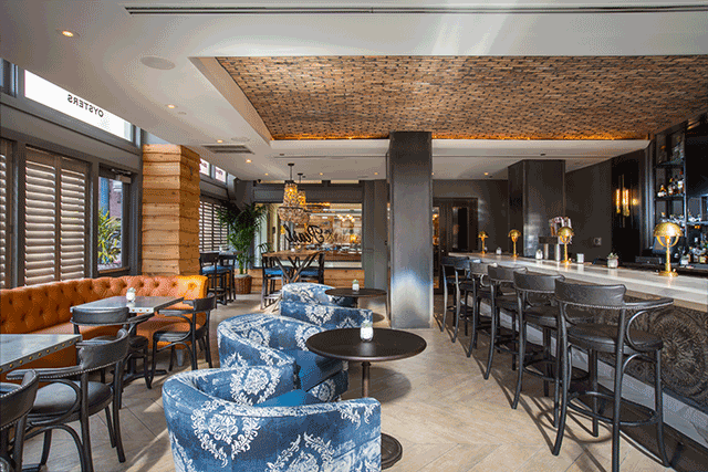 The Renovated Space Exudes An Urban Coastal Aesthetic With Furnishings And Details That Include Vintage Brass Light Fixtures Accents Caramel Colored