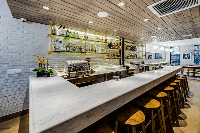 the 75 foot long dining room features a whitewashed brick wall that functions as the restaurants focal point the 10 seat white carrara marble bar links